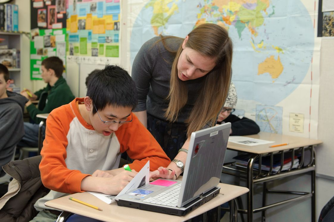 Edison High School Photo - A student works with history teacher Ms. Connolly during class. Every incoming student receives a laptop (now an iPad) equipped with assistive software.