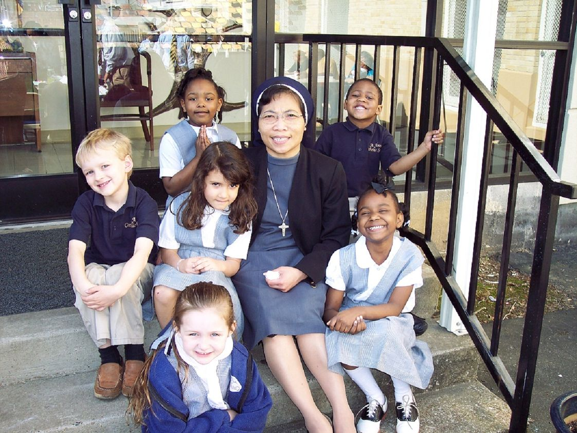 St Anne Elementary School Photo #1 - Preschool students sit on the steps with Sr. Ancilia Indrati while other students play at recess.