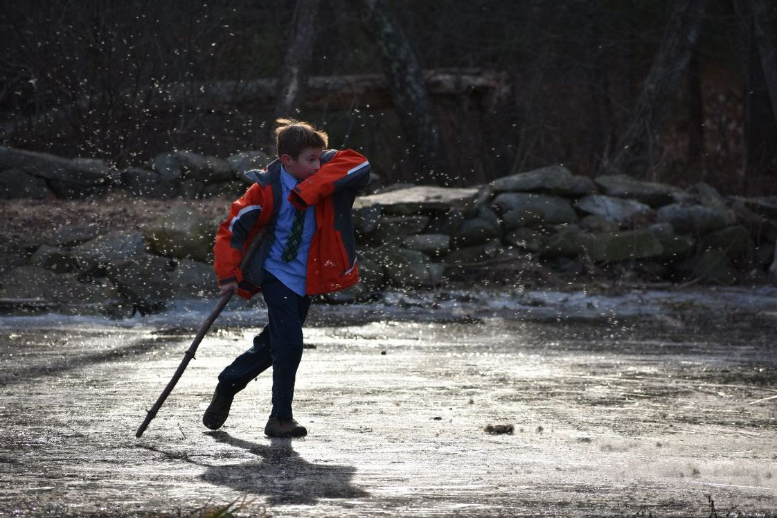 Sparhawk Academy Photo - A Sparhawk boy ventures forth onto a frozen brook on campus. Direct engagement with creation is a cornerstone of our curriculum.