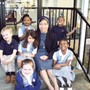 St Anne Elementary School Photo - Preschool students sit on the steps with Sr. Ancilia Indrati while other students play at recess.
